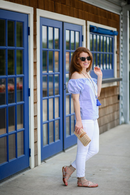 Design Darling wears a seersucker top, blue tassel necklace, white jeans, rattan clutch, and gold gladiator sandals