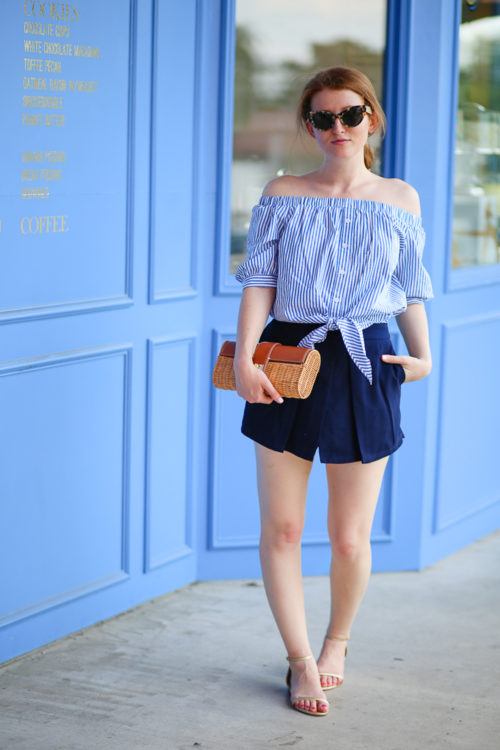 Design Darling wears a striped off-the-shoulder top from Tuckernuck, navy shorts by Cupcakes & Cashmere, a wicker clutch from J.McLaughlin, and pineapple sandals from Lilly Pulitzer