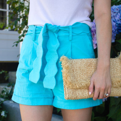 turquoise scalloped shorts with raffia clutch