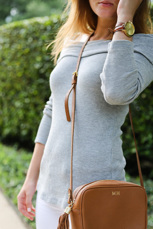 design darling wears a gray splendid off the shoulder top and gigi new york monogrammed cross body bag