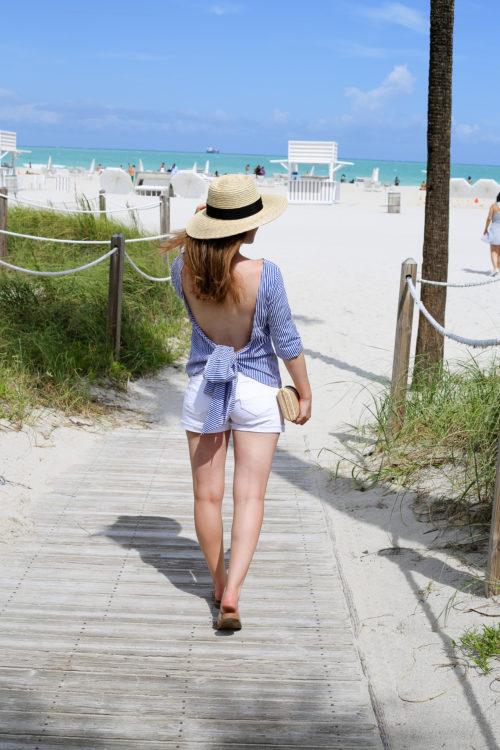 pixie market striped backless bow top with straw hat and white jean shorts