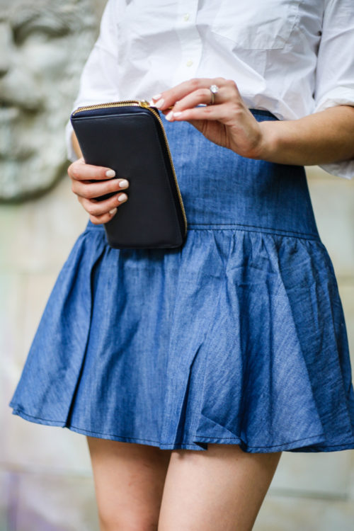 anthropologie tiered denim mini skirt with j.crew white shirt and cuyana navy wallet on design darling