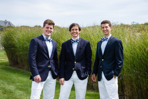 groomsmen in navy blazers and white pants