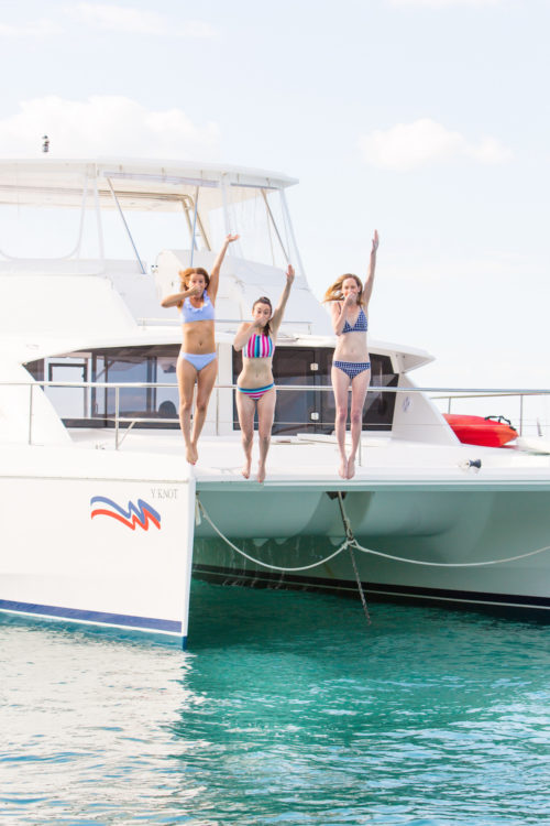 design darling jumping off boat in abacos