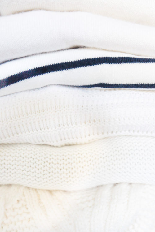 stack of white sweaters in design darling closet